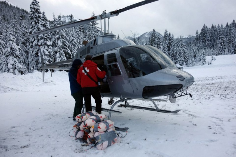 Crystal Mountain patrollers load large bags of explosives into a waiting helicopter last Friday. (photo: Crystal Mountain Resort)