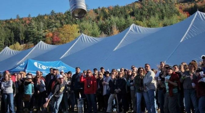 A participant in the annual Attitash Oktoberfest Keg Toss gives it all he's got to throw an empty keg as far as possible. (file photo: Attitash Mountain Resort)