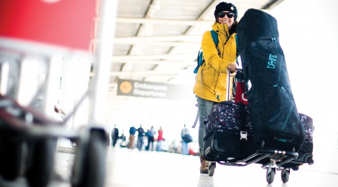 There must be some great pow awaiting, because we don't know anyone who smiles like this while lugging their skis and bags through an airport! (file photo: Dakine)