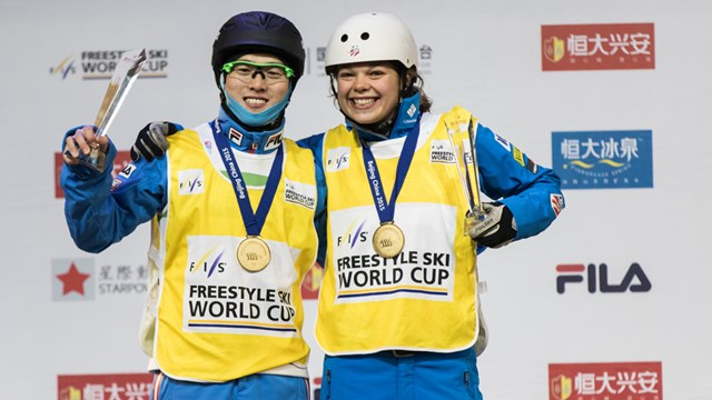 Ashley Caldwell (USA) and Guangpu Qi (CHN) wear yellow World Cup bibs after winning the aerials opener on Saturday in Beijing, China. (photo: Ronnie Yan/FIS)
