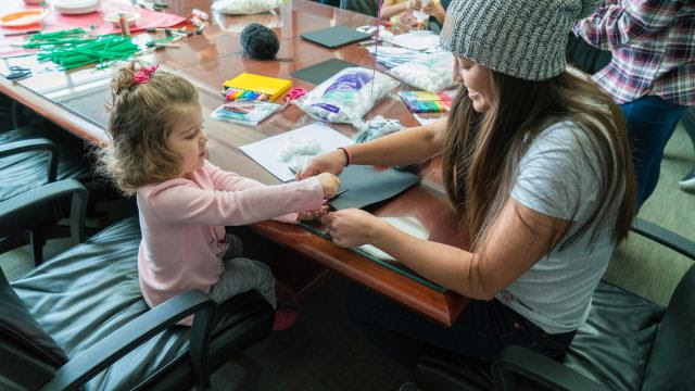 Aerials skier Kira Tanghe works on a cotton ball ghost Halloween craft with a patient. (photo: Primary Children's Hospital)